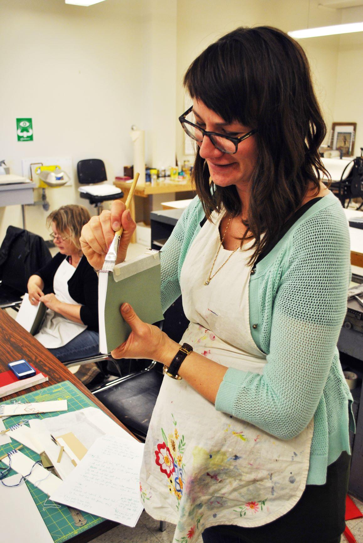 woman binding book with glue
